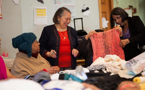 Carmen Barbosa teaches a knitting class at a time bank.