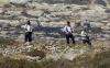 Armed settlers overlook a Palestinian village south of Nablus during confrontations following the setting on fire of Palestinian-owned fields on Jan. 1, 2010.