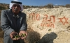 A Palestinian man displays olives in front of settler graffiti with a Jewish star of David and Hebrew writing that says 'price-tag' -- a term settlers use for their attacks on Palestinians, Sept. 29, 2011.