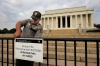 <b>Washington, D.C.</b> A National Park Service officer works on a sign announcing the closure of the Lincoln Memorial due to the shutdown.