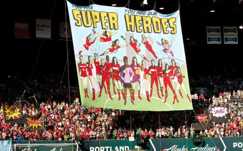 Fans of the Portland Thorns women's soccer team unfurl a banner honoring the team.