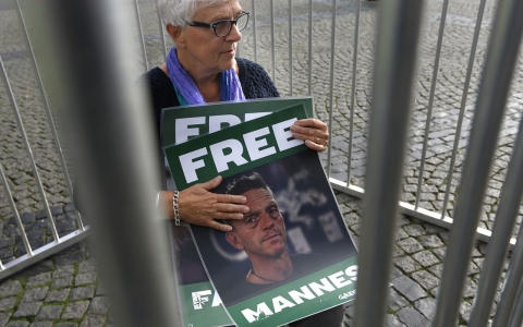 The mother of Dutch Greenpeace activist Mannes Ubels holds a poster with her son's picture as she demonstrates
