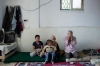 Syrian refugee Abu Mohammad, his wife and two sons sit in their one-room house in the village of Habaka, Jordan, on Oct. 2.