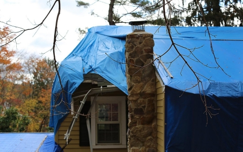 Eileen Lombardi's home remains covered with a tarp.