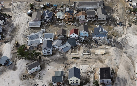Homes and roads overwhelmed by waves and sand after Superstorm Sandy.