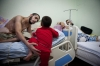Mustafa al-Shegh, 19, helps his 2-year-old cousin Ignue climb up to join him on a ward bed. Al-Shegh suffered spinal damage from shrapnel and is semiparalyzed from the waist down.