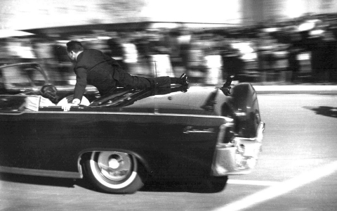 Secret Service agent Clint Hill climbs onto the back of John F. Kennedy's limo on Nov. 22, 1963, as it speeds away after the president was shot.
