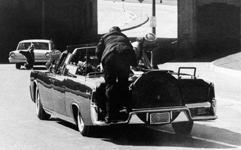 Clint Hill climbs onto the rear bumper of Kennedy's limo as Jackie stands up after shots are fired.