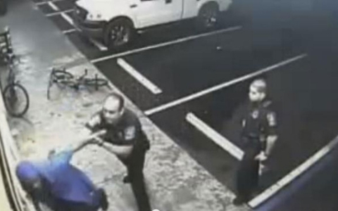Police officers stopping and searching a customer in a still from the store's video footage.
