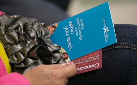 A woman holds a health insurance marketplace pamphlet at a community clinic in Takoma Park, Maryland.