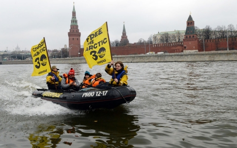 Greenpeace activists hold flags reading 'Free the Arctic 30' as they go past the Kremlin by boat to protest the detention of the 'Arctic 30'