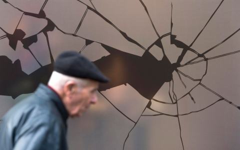 A man walks past a shop window decorated with a sticker simulating broken glass ahead of the 75th anniversary of the Kristallnacht pogrom