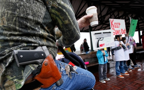 A man sits outside a Starbucks in Seattle with his gun holstered while children participate in an anti-gun protest.