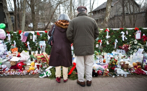 A couple stands at a memorial in honor of Sandy Hook's 26 victims last Christmas Eve.