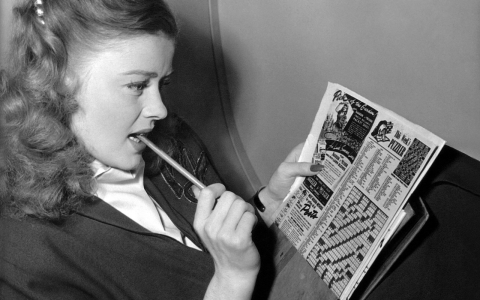 The actress Helen Walker puzzles over a crossword, circa 1940s.