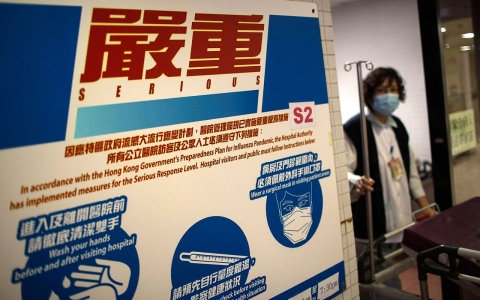 A medical officer walks past a sign showing an infection control notice alert level at the Princess Margaret Hospital on Dec. 4, 2013 in Hong Kong.