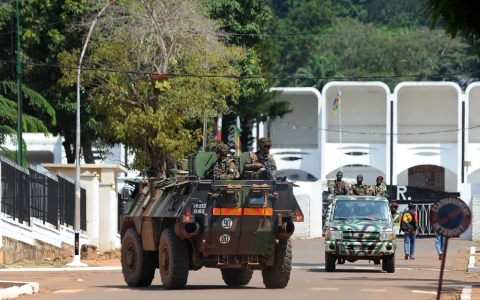 French soldiers in an armored vehicle pass ex-Seleka rebels in truck as they patrol in front of the presidential palace in Bangui on Dec. 8, 2013