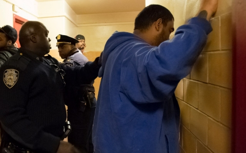 Two NYPD officers stop three people in the stairwell of 212 West 129th street. January 2013