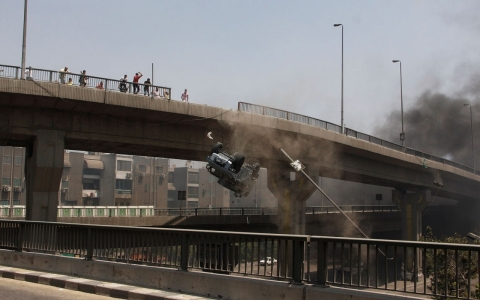 A police vehicle is pushed off of the 6th of October bridge by protesters close to Rabaa al Adawiya Square on Wednesday.