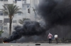 Members of the Muslim Brotherhood get away from a fire at Rabaa Adawiya square, in Cairo Wednesday.