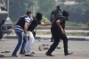 Riot police officers run during clashes with members of the Muslim Brotherhood and Morsi supporters at Rabaa Adawiya square, in Cairo Wednesday.
