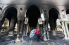 A man walks outside the burnt Rabaa Adawiya mosque, the morning after the clearing of a protest camp around the mosque, in Cairo, Thursday.
