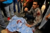 Egyptian Muslim Brotherhood supporters stand next to the body of a comrade who was shot during clashes with security forces in Giza district on the outskirts of Cairo, Friday.