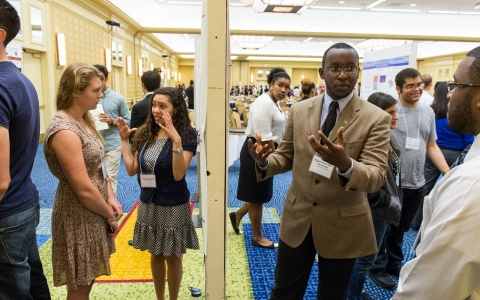 Miguel Twahirwa (MSRP '13 & '12), right, and Ellen Weburg (EBICS REU '13) present their work at the annual Summer Research Program poster session.