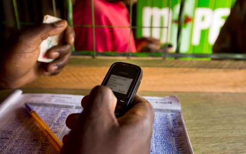 A resident uses a Nokia Oyj mobile phone to access the M-Pesa mobile banking application in Nairobi, Kenya, on Sunday, April 14, 2013.