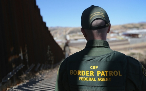 A Border Patrol agent patrols the fence dividing the U.S. and Mexico in Nogales, Ariz.