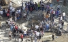 Residents gather around a crater caused by one of the two explosions outside one of two mosques in Lebanon's northern city of Tripoli, Aug. 23, 2013.