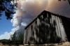 A plume of smoke from the Rim Fire rises above an outbuilding on Friday.