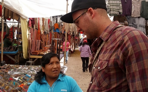 Nick Farmer, who knows more than 15 languages, speaks Quechua with a vendor at a market in Peru.