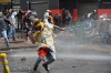 A demonstrator throws stones at the riot police during clashes that erupted during a march in support of Colombian farmers on Thursday.