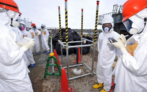 Local government officials and nuclear experts inspect a monitoring well Tuesday at Tokyo Electric Power Company's Fukushima nuclear plant.