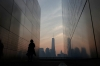 A woman looks at victims names on the wall of the 9/11 Empty Sky memorial at sunrise across from New York's Lower Manhattan and One World Trade Center in LIberty State Park in Jersey City, New Jersey.