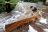 Jake Bennett drops a sand bag down to help funnel water down a street on Thursday in Boulder, Colo.