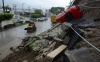A car lies precariously on its side after part of a hill collapsed because of heavy rains in Acapulco on Sunday.