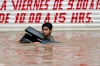 A young man carrying a stolen computer wades through a flooded street.