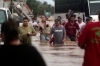 Residents and tourists wade through a flooded street in Acapulco, Guerrero state, Mexico, after heavy rains hit the area.