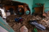 People stand in a house flooded by mud after a mountain landslide in Altotonga in Veracruz state.