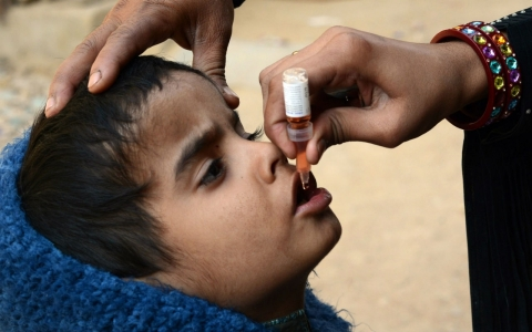 A Pakistani health worker administers polio vaccine drops to a young child at a polio vaccination center in Karachi on January 8, 2013.