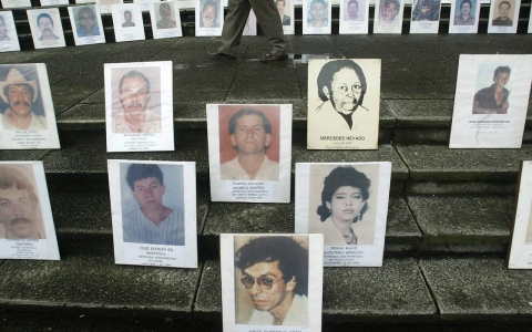 A pedestrian walks amid portraits of people disappeared during the armed conflict in Colombia.
