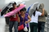 A woman struggles to control her umbrella on an overpass in the rain in Manila.