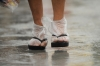 A Manila woman uses plastic bags to keep her feet from getting wet.