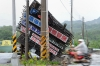 A motorcyclist rides past a billboard damaged by Usagi's strong winds in Pingtung County, Taiwan.