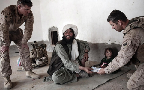 US Marines give an Afghan imam funds to pay for repairs to a mosque damaged during an offensive against the Taliban in Marjah, Afghansitan, 2010.