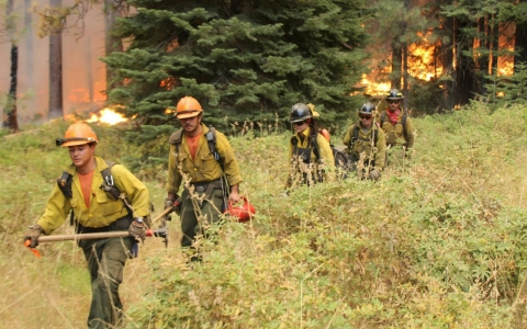 Firefighters hike away from a section of the Rim Fire in Yosemite National Park on Sunday.