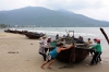 Fishermen and women pull a boat ashore on Tho Quang beach in Vietnam's central city of Danang Monday.