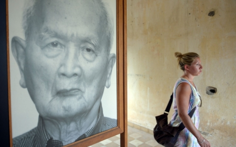 A tourist walks past a portrait photo of former Khmer Rouge leader 'Brother Number Two' Nuon Chea.